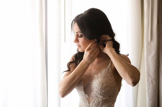 bride-in-galia-lahav-sheer-wedding-dress-putting-on-earrings-in-front-of-sunny-window