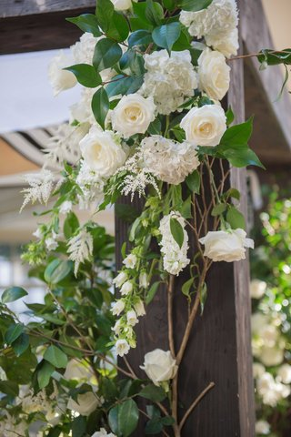 varying-white-flowers-and-green-foliage-winding-up-a-wooden-chuppah-at-a-couples-jewish-ceremony