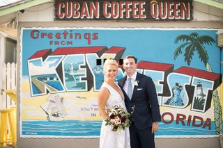 bride-and-groom-taking-portrait-in-front-of-cuban-coffee-store-with-post-card-greeting-mural-on-wall