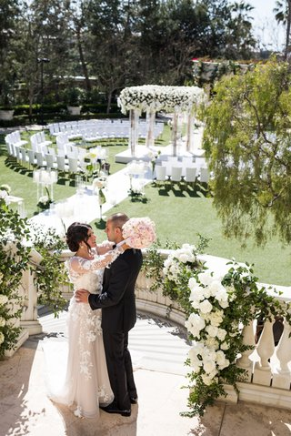 wedding-ceremony-with-bride-and-groom-on-top-of-staircase-guests-in-the-round-white-chairs-flowers