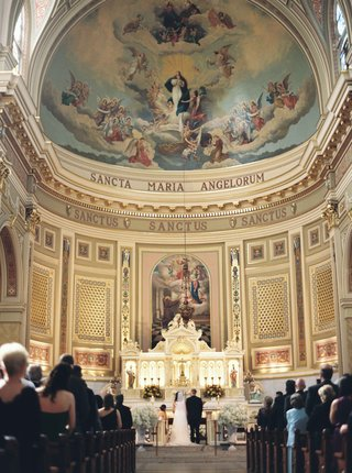 bride-and-groom-kneel-at-altar-for-st-mary-of-the-angels-catholic-church-in-chicago