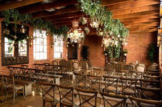 wood-beams-brick-wall-urban-chic-wedding-ceremony-venue-chandelier-greenery-vineyard-chairs-benches
