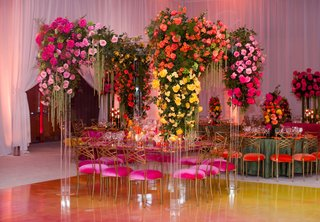wedding-reception-pink-velvet-cushion-with-yellow-orange-pink-flowers-lucite-arch-arbor-ballroom