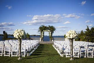 outdoor-ceremony-set-up-overlooking-atlantic-ocean-lawn-chairs-tall-vases-floral-arch