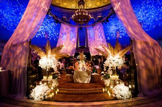 wedding-reception-drapery-with-bright-lights-pink-blue-drapery-gold-palm-leaves-white-flowers-guests