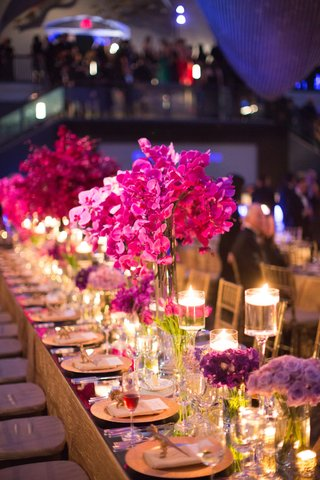 wedding-reception-table-with-a-mirror-top-floating-candles-and-purple-flowers