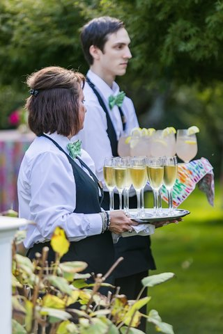 servers-holding-trays-of-champagne-and-cocktails-lemon-green-bow-ties-outdoor-cocktail-hour
