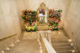 candles-on-steps-and-floral-walls-next-to-gold-mirror
