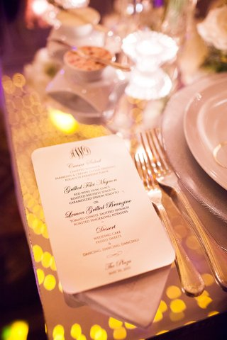 menu-for-wedding-reception-dinner-on-top-of-reflective-clear-table-with-reflection-of-lights