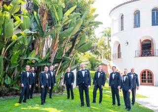 groom-and-groomsmen-in-navy-blue-suits-with-black-bow-ties-yellow-boutonniere-flowers-santa-barbara