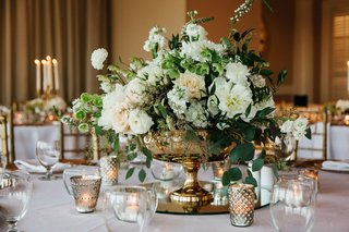 ivory-peony-and-rose-flowers-with-greenery-in-gold-footed-vase-white-tablecloth-candle-votives