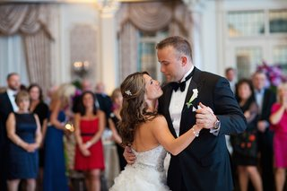 bride-in-a-strapless-lazaro-dress-with-beaded-bodice-dances-with-groom-in-black-tuxedo