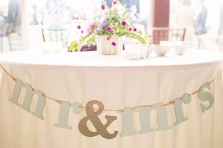 lyndsy-fonseca-and-noah-bean-wedding-reception-sweetheart-table-mr-and-mrs-banner-glitter-purple