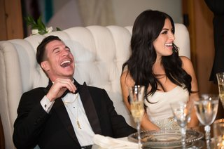 groom-laughs-during-wedding-toasts-tufted-white-loveseat-furniture