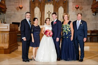 bride-in-a-line-gown-groom-in-navy-suit-with-parents-mothers-of-bride-and-groom-in-navy-church