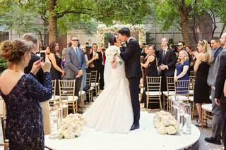bride-and-groom-share-kiss-platform-in-middle-of-outdoor-aisle-low-roses-after-vows