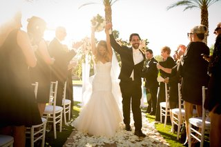 bride-and-groom-raising-hands-in-celebration-up-aisle
