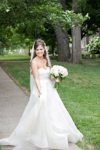 a-beautiful-bride-shows-off-her-delicate-a-line-wedding-gown-outside-the-church