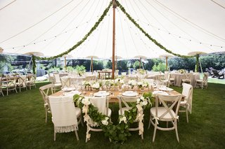 dinner-reception-tent-with-wood-tables-and-chairs