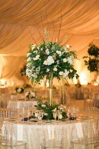 wedding-reception-clear-chairs-tall-gold-stand-with-greenery-verdure-white-flowers-branches-tent