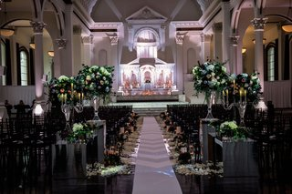wedding-ceremony-at-vibiana-altar-lighting-flower-arrangements-on-risers-petals-along-aisle-runner