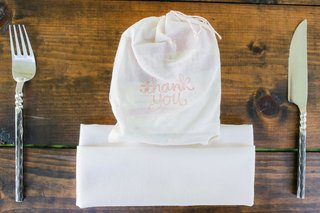 wedding-reception-seating-wood-table-white-muslin-bag-with-pink-thank-you-sign-at-place-setting