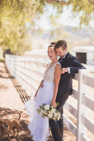 bride-in-mira-zwillinger-wedding-dress-from-carines-bridal-atelier-with-groom-in-front-of-fence