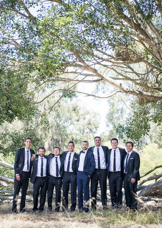 groom-navy-blue-tuxedo-groomsmen-black-tuxedos-stand-together-in-forest-in-santa-barbara