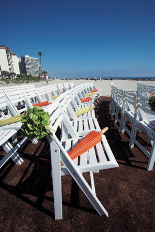 rows-of-white-wooden-chairs-with-umbrellas-at-beach-ceremony