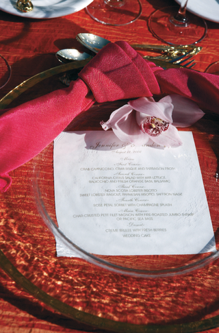 glass-charger-over-red-tablecloth-with-red-napkin-and-pink-flower