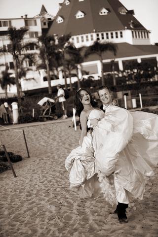 groom-carries-bride-across-sand-at-hotel-del-coronado