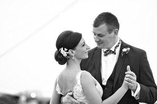 black-and-white-photo-of-bride-with-an-updo-and-floral-headpiece-dance-with-groom-in-suit-plaid-bow
