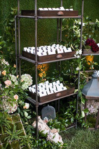 wedding-reception-escort-cards-in-wood-tray-on-industrial-book-shelf-hedge-wall-fall-flowers-green