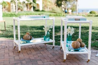 white-bar-carts-outside-with-seashell-escort-place-cards-in-blue-trays-with-rope-circle-decor