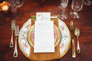 wedding-reception-place-setting-with-floral-china-golden-charger-flatware-napkin