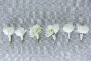 white-floral-boutonniere-ranunculus-flowers-wrapped-with-white-ribbon-for-groom-and-groomsmen