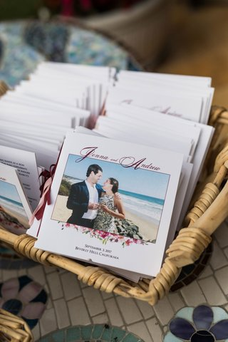 basket-filled-with-ceremony-programs-for-outdoor-wedding-photo-of-bride-and-groom-at-beach