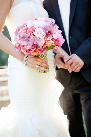 bride-in-a-sleeveless-vera-wang-dress-with-bouquet-of-pink-light-purple-orchids-roses-peonies