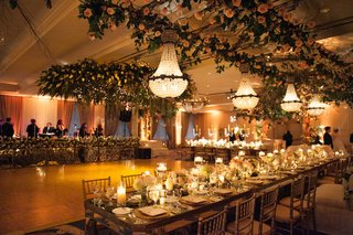 long-head-table-with-chandelier-and-flowers-hanging-from-ceiling