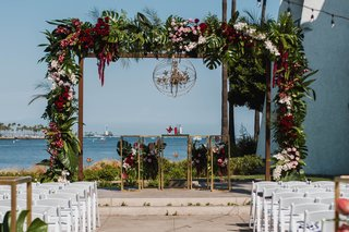 unique-chandelier-in-sphere-display-large-wedding-arbor-chuppah-with-tropical-leaves