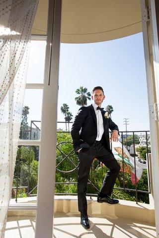 groom-in-lanvin-tuxedo-stands-on-balcony-of-hotel
