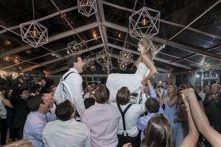 bride-and-groom-lifted-on-chairs-during-the-hora-in-a-clear-top-tent