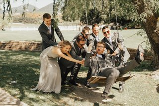group-of-groomsmen-and-groomswoman-in-grey-push-groom-on-wooden-swing