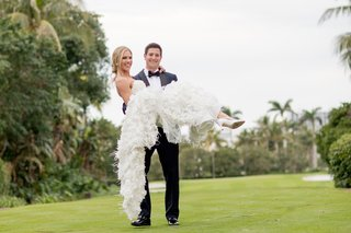 bride-in-marchesa-wedding-dress-carried-in-the-arms-of-her-groom-in-tuxedo