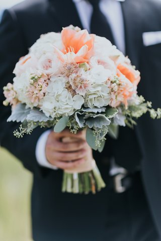 groom-holding-peach-bridal-bouquet-with-white-hydrangeas-dusty-miller-garden-roses