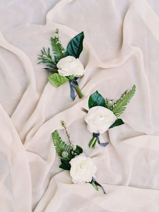 white-ranunculus-boutonniere-with-green-leaves-and-ferns-blue-ribbon