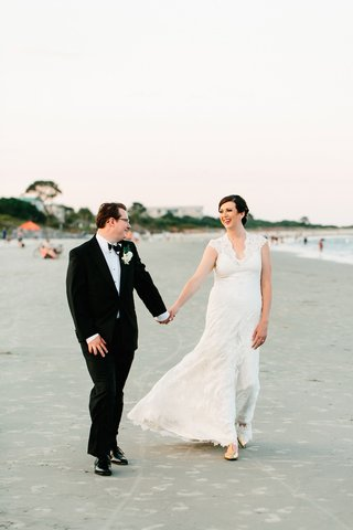 bride-in-v-neck-lace-wedding-dress-with-groom-holding-hands-with-sand-on-beach-in-georgia