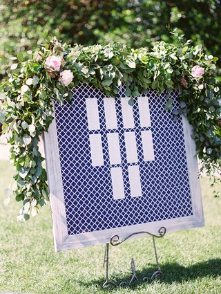 blue-and-white-geometric-pattern-print-in-greywash-frame-greenery-on-top-seating-chart-easel-grass