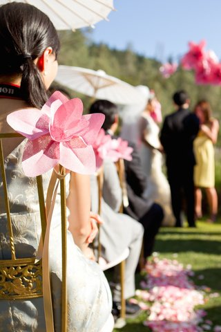 outdoor-wedding-ceremony-with-blush-paper-daffodils-tied-to-chairs-along-the-aisle