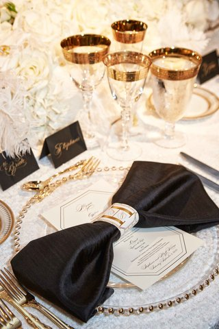 place-setting-with-white-table-cloth-black-napkin-gold-flatware-charger-plate-glassware-bow-detail
